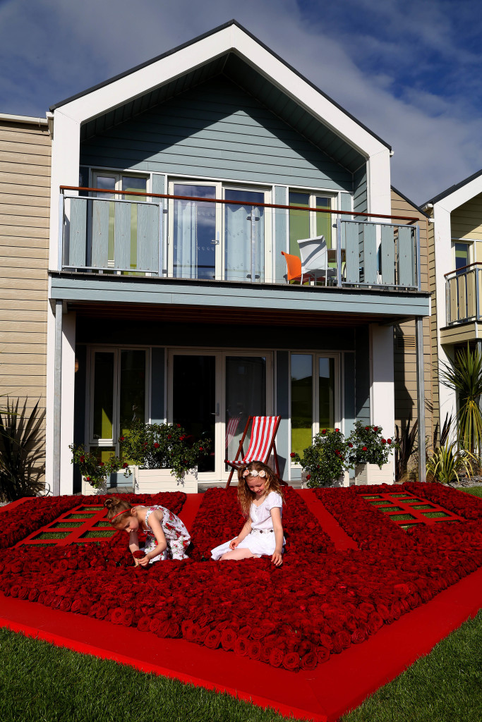 EDITORIAL USE ONLY (Left to right) Lilly-Grace Perkins aged 5 and her sister Sienna Perkins aged 8 from Minehead enjoy some family time in the installation of Sir William Butlin roses at the new West Lakes Chalet Village on Butlin's Minehead resort in Somerset. PRESS ASSOCIATION Photo. Picture date: Tuesday May 12, 2015. Exactly 1,936 of the newly commissioned roses form a 10x10ft scale replica of Billy Butlin's original chalets, which he unveiled to British holidaymakers in 1936 and each chalet was surrounded by its own garden of roses to create a home from home for families. The rose has been commissioned to commemorate the launch of the new £16 million chalet village, and will be planted across Butlin's resorts with some of the blooms to be sold to raise money for Great Ormond Street Hospital, Billy's favourite charity and Butlin's official charity partner for 2015. Photo credit should read: Geoff Caddick/PA Wire